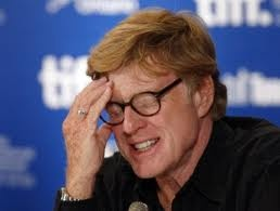 """Robert Redford: emotion of frustration has components of anger, disappointment, denial and conflict.  Fingers are brought to his forehead, thumb to his cheek, physical metaphor for frustration/pain. Lower teeth are barred, jaw is protruding slightly consistent with mild anger. Head tilted downward is also indicative of negative emotional tone. Eyes are closed = visual blocking. We don't like what we see or visually remember in our """"mind's eye."""""""