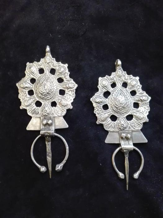Paar zilveren Beber kuitbeen - Marokko - mid 20ste eeuw  Kuitbeen zijn decoratieve symbolische en functioneel. De grootte en het gewicht van de broche gedragen door Berber vrouw transactiestatus haar terwijl hun vorm de vorm in het algemeen vertegenwoordigen de vrouwelijke vorm. ook dienen ze als gespen haar mantel in plaats te houden. Ambachtslieden in het anti-Atlas gebergte zijn gespecialiseerd in deze ongebruikelijke vorm van decoratie met veel fijne openingen - een tijdrovende techniek…