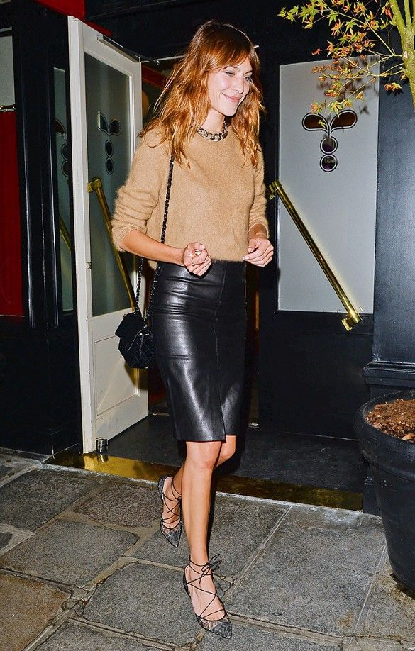 Alexa Chung rocking a simple outfit with a leather skirt and fuzzy sweater.