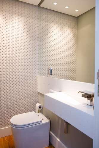 os azulejos antigos foram substituídos por porcelanato com alto relevo que parece um papel de parede. Ele foi colocado no fundo do cômodo para que fosse refletido pelo espelho, criando uma sensação de ilusão de ótica