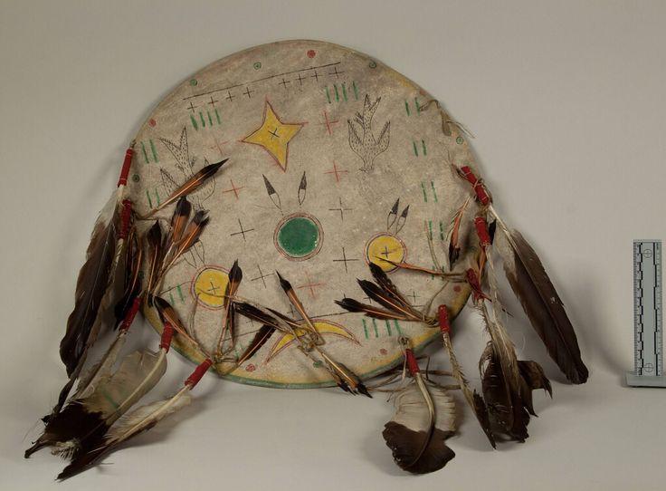 """Щит c покрышкой, Шайены. Вид два. Из """"Oklahoma Historical Society, Temple Houston Collection"""". Дизайн щита включает птиц, геометрические фигуры, полумесяц. Цвета: жёлтый, красный, чёрный, зелёный. Ремни на краях щита, орлиные перья.  Донор Victor J. Evans. Щит был изготовлен White Horse, незадолго до его смерти.  Дата поступления 20 Maрта 1931 года.  NMNH - Anthropology Dept."""