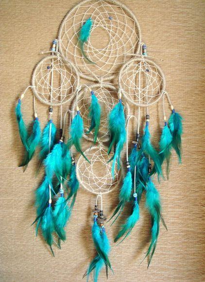"""""""HOLLY WATER"""" Filtro dos Sonhos ou Dream Catcher  Trabalho manual inspirado na tradição indígena norte-americana que, segundo a lenda descrita abaixo, protege e filtra os sonhos durante o período de descanso e neutraliza as energias ruins do ambiente.  Com cinco aros interligados, sendo o maior com 17 cm de diâmetro, o intermediário com 12cm de diâmetro e os 3 menores com 9cm de diâmetro cada um, esse modelo é feito com sisal, penas azuis mescladas, contas de cerâmica e madeira, sementes e…"""