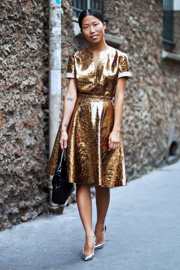 A Gold Dress Is Worn With Black Purse And Silver Stilettos