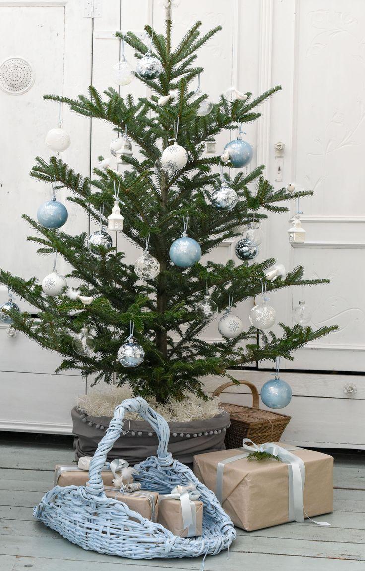 Le sapin de Noël dans les tons hivernals: blanc et bleu dans l'esprit de chalet de montagne.