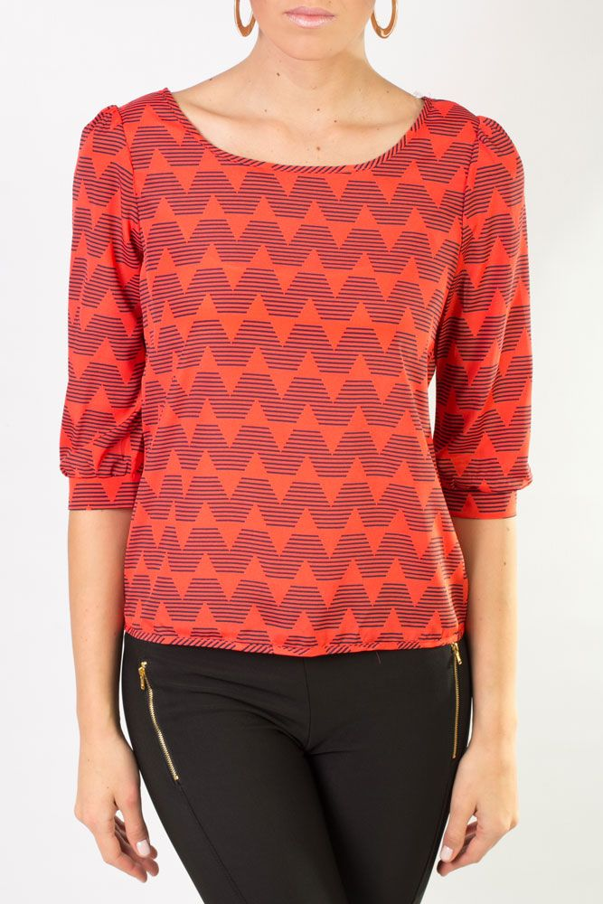 Blusa anaranjada con diseños en color negro, cuello redondo y manga tres cuartos.