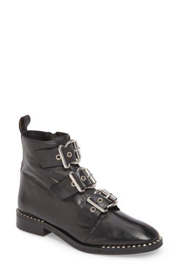 Pyramid studs trace the sole of an eye-catching moto boot finished with three oversized buckle straps at the vamp.