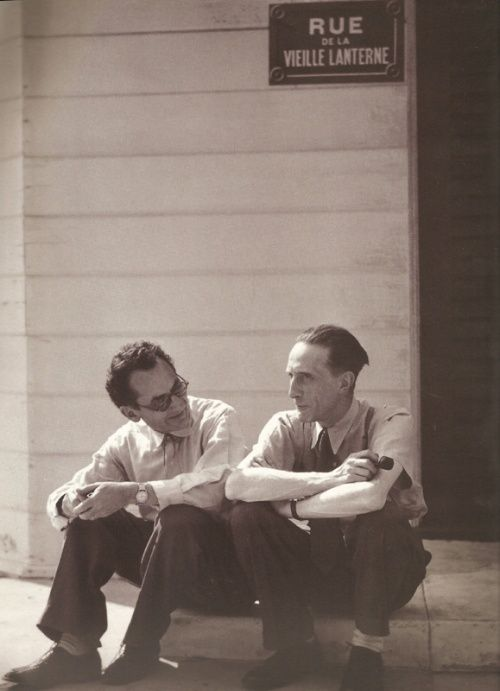 "Man Ray and Marcel Duchamp sitting beneath a Parisian street sign, ""Rue de la Vieille Lanterne"", on a stage set in Hollywood. L.A., California, 1949"