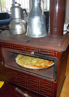 Cooking traditional Turkish borek in a wood burning oven while the ever-present black tea kettle awaits perched atop another boiling kettle of water