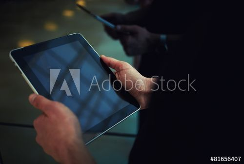 Business man working on touchpad in elevator, digital tablet