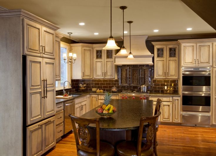 french cream antiqued painted wood cabinetry featuring espresso finished kitchen island on kitchen ideas cabinets id=19813