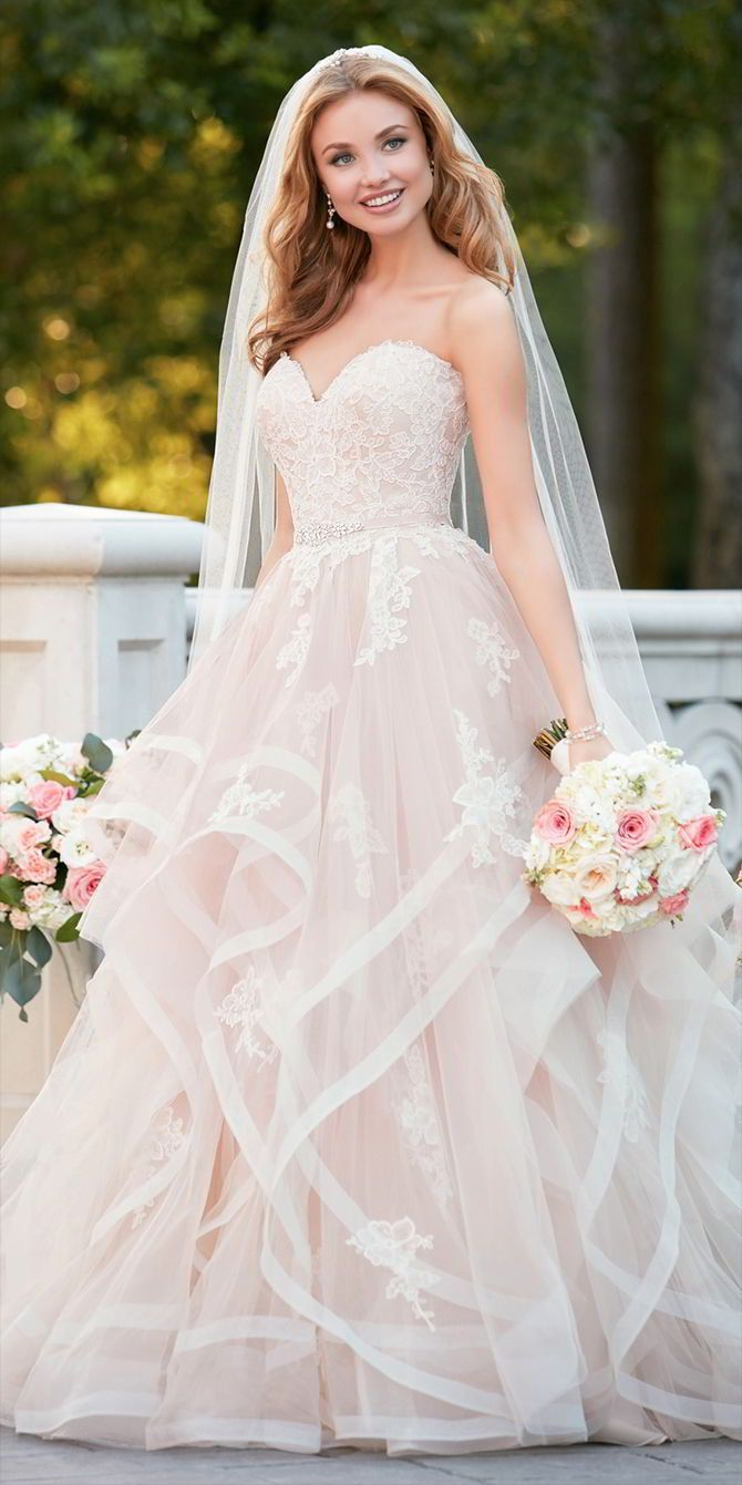 This pink floral lace wedding dress with textured skirt from Stella York is a masterpiece! The fun and frothy layers of tulle create a skirt full of big, yet soft texture that is complemented by lace motifs throughout, adding volume and interest. Lace and tulle over Regency organza make this ball gown a dream dress for the bride wanting blush tones on her wedding day. Diamante beading throughout give a subtle sparkle while the double horsehair detail on the skirt is reminiscent of couture…