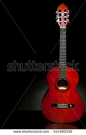 Damian Gretka. Microstock Photography. lonely musical instrument which is a guitar on a black background / acoustic guitar, stringed instrument
