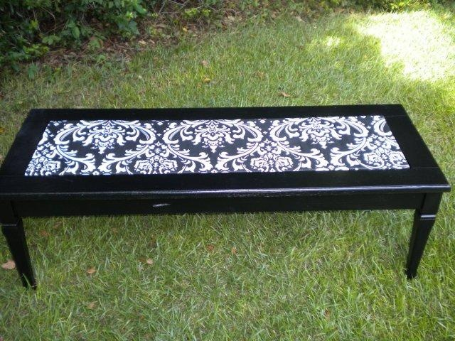 Old coffee table made into a fun coffee table.  This is with a coat of black spray paint...and with fabric covered plywood (coated in mod podge) placed in the middle.