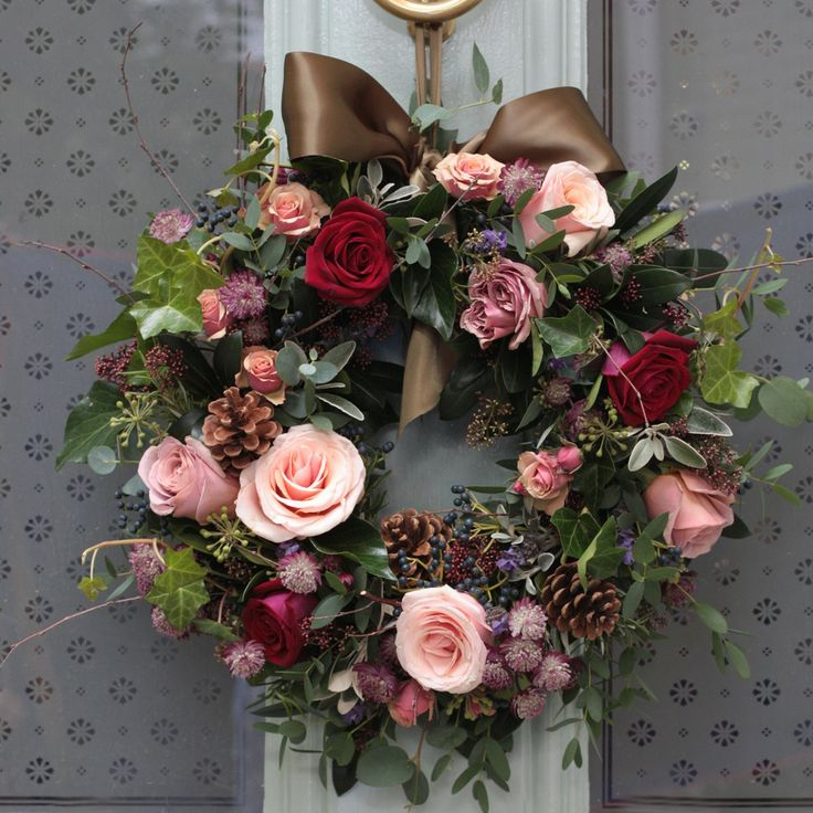 The Real Flower Company Red & Antique Luxury Door Christmas Wreath is an absolute favourite here at The Real Flower Company. A beautiful combination of scented red and antique rose heads arranged with astrantia, skimmia, rich berries, pine cones and finished with ivy trails, herbs and seasonal foliage. A stunning welcome to your front door this Christmas. Once the flowers have faded the foliage will continue throughout the festive period. The diameter of the wreath will be around 15 inches…