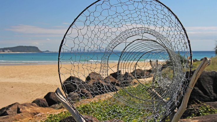 A tunnel of wire mesh weaves its way across the rocks as part of the Swell Sculpture Festival on the Gold Coast. (Photo: ABC/Damien Larkins.)