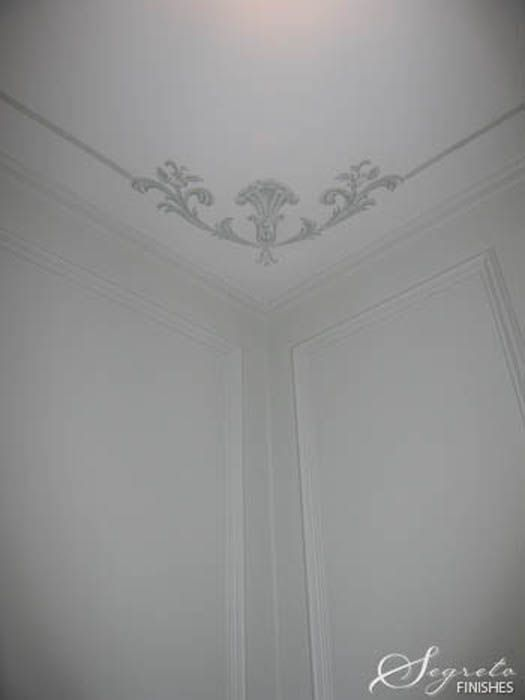 Corner treatments are great for low ceilings - they lift the eye, making the room appear taller. In this room, we painted a special flourish at each corner and connected them by a simple line detail to further define the space.  ~segretosecrets.squarespace.com