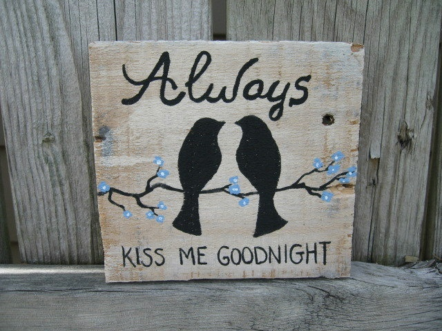 "This old barn wood farm sayings sign is painted with two little love one another birds on a branch with blue blossoms. It reads, ""Always Kiss Me Goodnight."""
