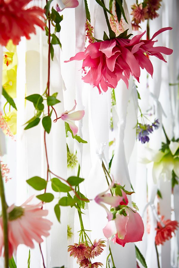 This take on a low-budget DIY dorm room update creates a hanging garden. Need some privacy from your chatty roommate? How about a mood booster? Try a simple room divider made from a curtain and faux flowers. Hang the curtain from a rod, cutting it into strips and leaving the top intact so it can still be pulled back and forth. Simply knot as many stems as you like into each strip.