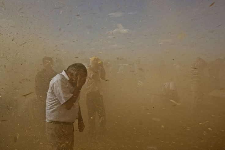 refugees fleeing to Turkey Photo: Syrians endure a sandstorm near the village of Dikmtas.