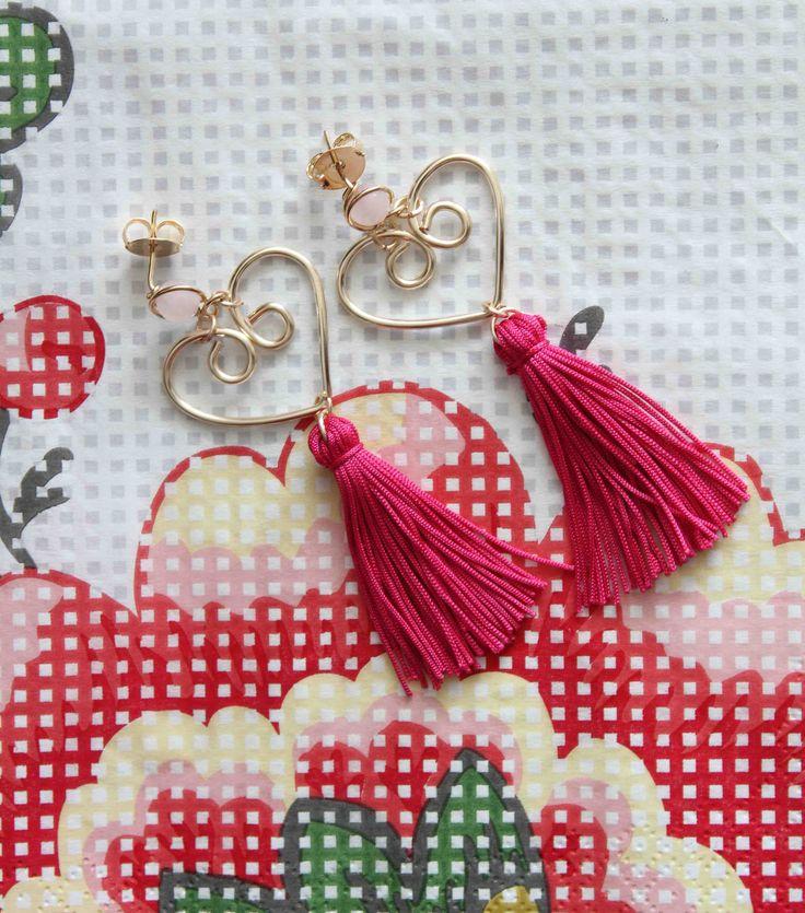 Pendientes elaborados a mano en hilo de cobre con baño de oro amarillo, pequeño cuarzo rosado del cual penden un corazón hecho con hilo de cobre bañado en oro, y a su vez borlas largas de hilo de seda.