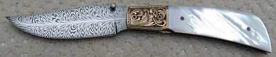 """Kevin Casey #5 """"Angel wing"""" folder. 3 1/5"""" Feather Damascus by maker with Premium MOP scales. Hand engraved bronze bolsters file worked and anodized liners with engraved bronze back spacer. Opal thumb stud. Engraving by Ken Hurst. Overall length is 7 ½"""",  folded length is 4 ¼""""."""