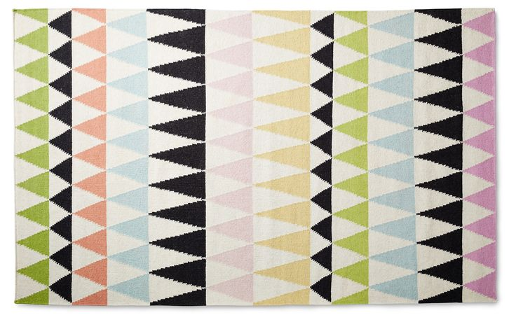 A bold geometric design in a colorful palette make this wool rug an appealing contemporary foundation for any space. Handwoven in India. A rug pad is recommended to keep this securely in place.