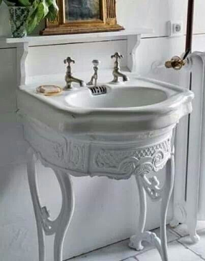 Pedestal sink top, but on an old sewing machine stand (painted white).  Add ledge shelf above.