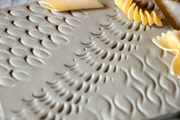 A simple and brilliant idea to be realized at school with clay slabs: colored tiles imprinted with different shapes of pasta. Farfalle, penne, fusilli or spaghetti become interesting tools to creat…