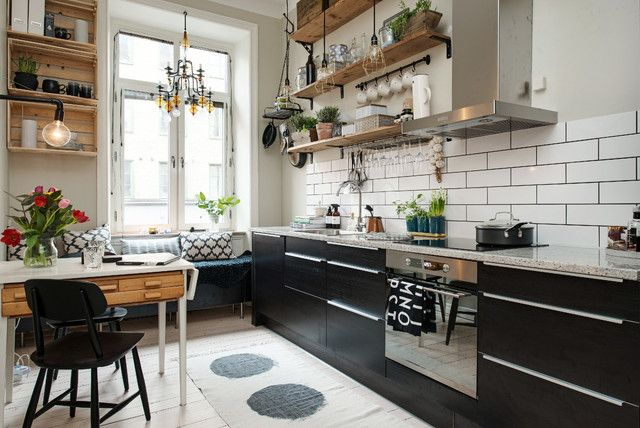 This is an example of a scandinavian kitchen with a drop-in sink, flat-panel cabinets and black cabinets.