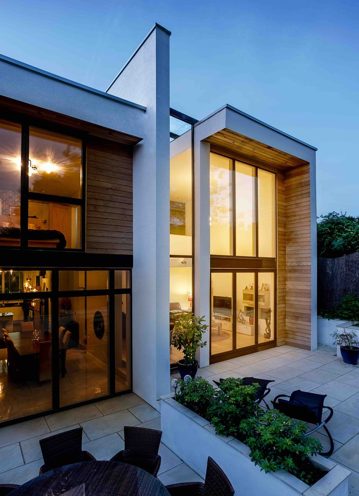 This 2-storey house with flat roof comprises of 2 long 'wrapping' elements that stretch down the narrow site; the white rendered 'wraps' contain all the living and sleeping accommodation and are infilled with cedar panels and large expanses of glazing at each end. Set between is a double-height glazed circulation atrium that runs through the middle of the house, linking the spaces together and creating a connection between front and rear.