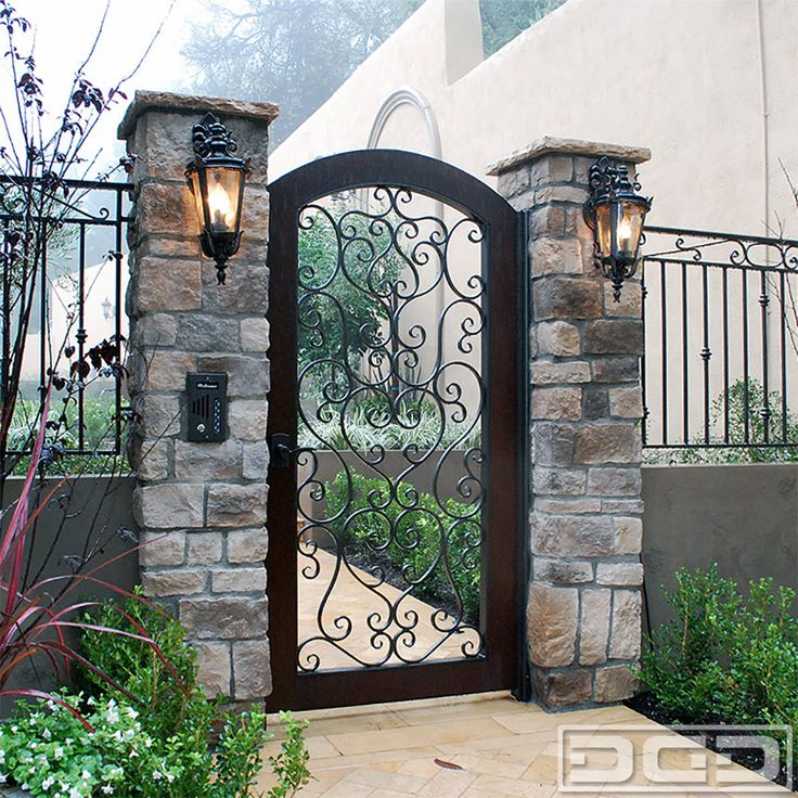 Perfect for a Spanish Mediterranean Style Home this wood andiron entry gate comes with hand-forged iron scrolling throughout. It is beautifully finished with a dark stained mahogany wooden frame and subtle arched top. This Mediterranean Garden Gate serves as a security element that blends well into the beautiful Mediterranean architecture of this estate. Optionally, we …