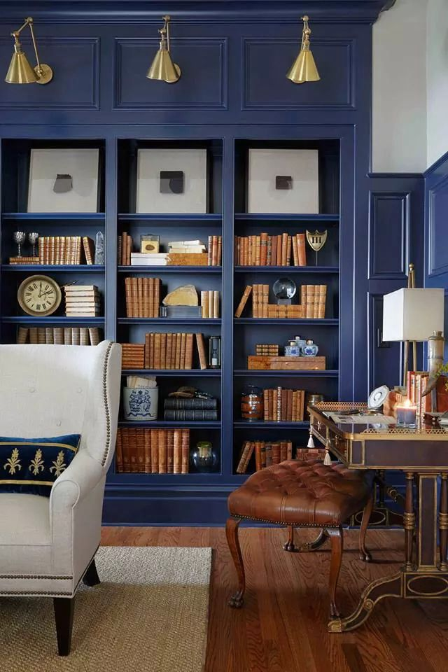 Deep blue bookshelves and wainscoting makes a statement.  #homefeatures #builtins #wainscoting