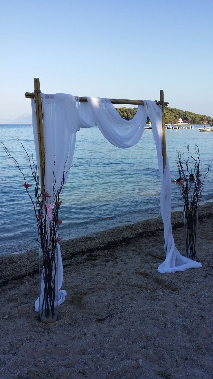 Beach wedding with white fabric, wooden arch and delicate pink flowers