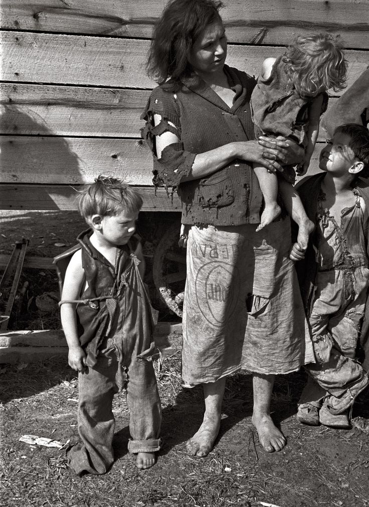 """March 1936. """"Mother and baby of family of nine living in field on U.S. Route 70 near the Tennessee River.""""   This picture is amazing, look at their clothes and the dirt."""