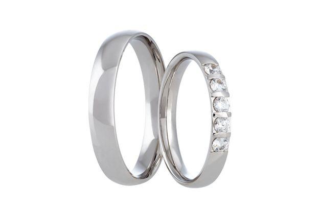 Snubní prsteny z bílého zlata s celolesklým povrchem. Do dámského kroužku je fasováno pět oslnivých kamenů.