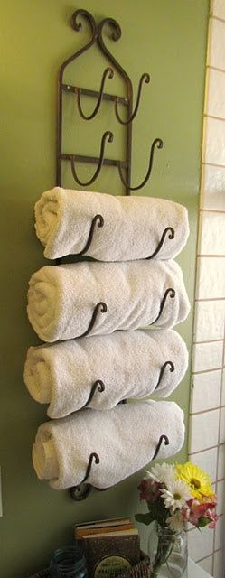 Wine rack towel holder - perfect when guests come and could also hang used towels on it too.... how pretty is this for bathroom decor, or for your kitchen towels.... yard sales, thrift shops are great places to find wine racks, sometimes wood, other times wire or wrought iron, also antique stores have vintage ones from time to time... cute!