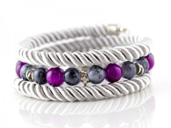 Bransoletka wykonana ze sznurka skręcanego, koralików szklanych oraz elementów w kolorze srebrnym. ...