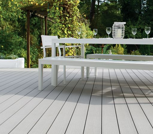 A very modern outdoor dining area, complete with VertiGrain Grey deck boards from TimberTech UK.