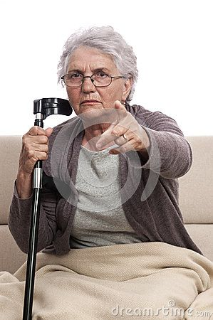 Accusatory disabled old woman with crutch support, sitting on couch and pointing. Blanket on feet. Isolated on white.