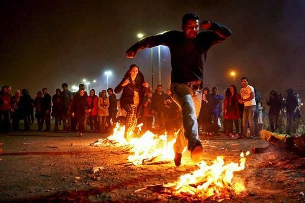 People jumping over bonfires in Iran. This is an ancient Zoroastrian traditional festival. On the last Tuesday of the Persian New Year, people jump over  bonfires. Symbolically,   the fire would  take the pallor, sickness, and problems and in turn would give  warmth and energy.  The efforts by the Iranian regime to eliminate such festivities have resulted in more intense celebrations and a day of significant confrontation with the regime.