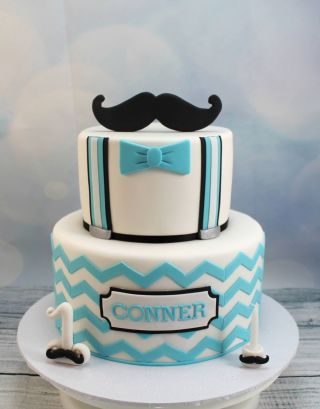 This cake was made to match a little man's 1st birthday party invitations. It has blue chevron stripes on the bottom tier and braces and bow tie on the front of the top tier, which matched the little man's outfit. Topped off with a moustache. The...