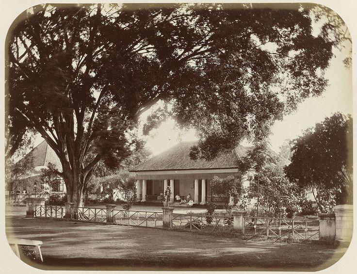 Woodbury & Page | Huis aan de Molenvliet, Woodbury & Page, 1870 - 1879 | Een huis aan de Molenvliet Oost te Batavia. Voor het huis een zeer grote boom, op de trap zit een gezin met kinderen. Ingeplakte foto in het fotoalbum getiteld: Gezichten van Java.