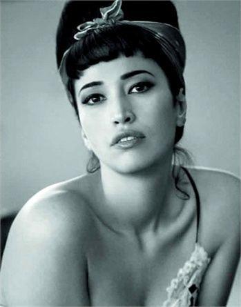 A cavallo tra gli Anni'50 e '60 c'è il look di Nina Zilli: ispirazione glam per una pin-up dei giorni nostri. Bello il raccolto cotonato con mini frangia e bandana stretta in un fiocco.
