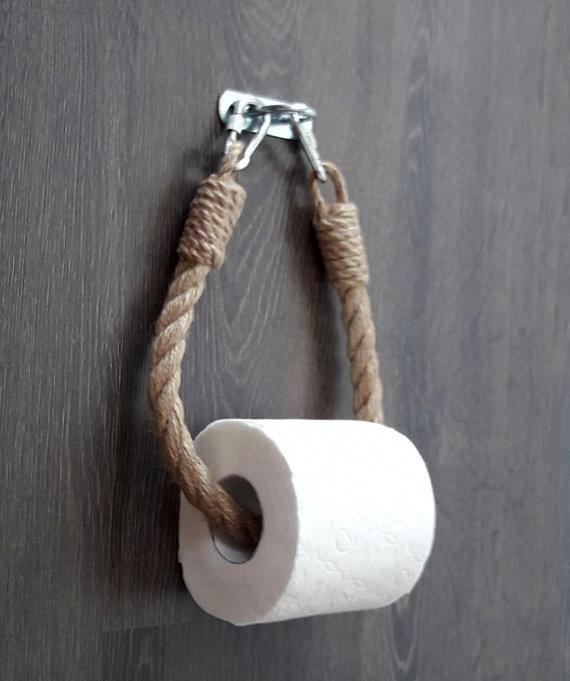 Der Toilettenpapierhalter besteht aus natürlichem Jute-Seil und einer Metallklammer aus