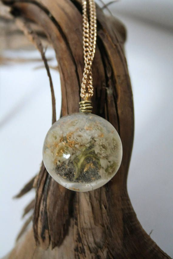 Pressed and dried white cottony wildflowers grown and harvested on the West coast of BC, encased in a clear circle-shaped, resin pendant with gold leaf flakes. All pieces are made one at a time and entirely by hand, embedded with locally sourced objects. Each piece is sanded from 220