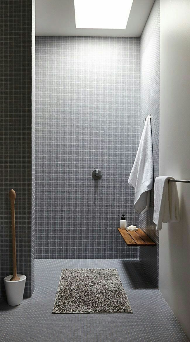 Very cool minimalist shower! The tiny tiles are really cool, & I love the little low shelf on the wall. So useful & pretty! Whoever put that there is a genius!