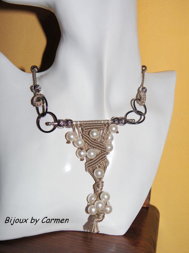 collana dal sapore un po' etnico realizzata a macramè, con inserti di perle bianche. contiene un elemento di riciclo ricavato dalla stanghetta di un ombrello....