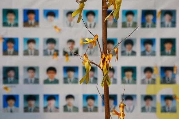 Portraits of students who died in the Sewol ferry disaster are seen behind an art installation dedicated to the victims in central Seoul. The captain of the ferry that capsized in April killing 304 passengers was jailed for 36 years after a court found him guilty of negligence. (2014 Kim Hong-Ji/Reuters)