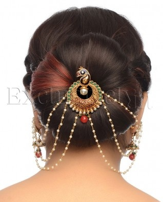 What a beautiful large low bun with beautiful ornaments! Care however should be taken before adopting such hairstyles, as due to it's high static charge, it will cause phlegm to move up in the throat, causing the voice to quaver & a frequent urge to clear the throat. A heavy chabi chhalla with a long & wide hook if inserted at the edge of the pleats of the saree, will reduce this problem as it's hook will activate the acupressure points that act to keep the throat clear.