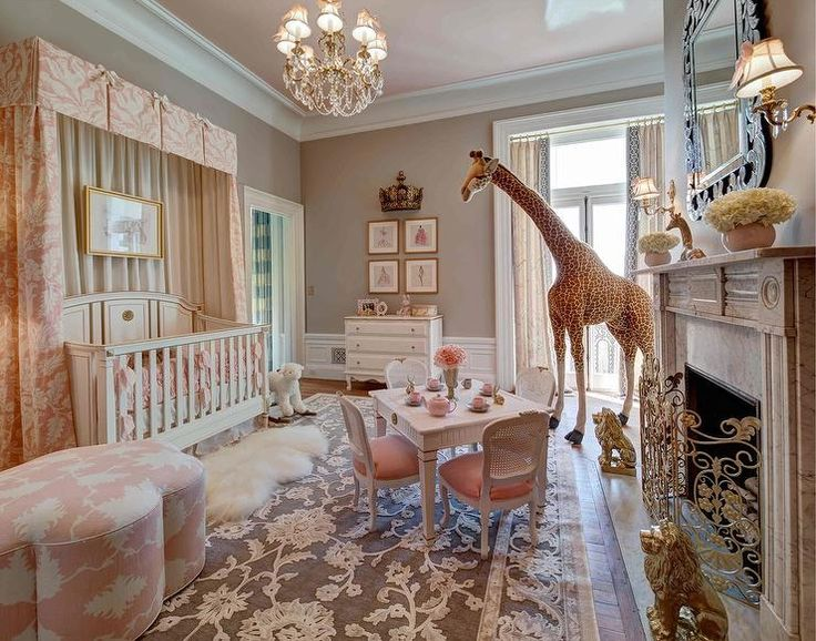 French nursery features a pink ceiling painted Benjamin Moore East Lake Rose over walls painted Benjamin Moore Smokey Taupe lined with a French crib dressed win Restoration Hardware Baby & Child Washed Appliquéd Fleur Nursery Bedding Collection accented with a pink pleated valance and pink curtains paired with a pink clover ottoman upholstered in Mary McDonald Garden of Persia Fabric atop a cream and brown rug.